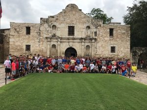 Crusaders take a photo in front of The Alamo.